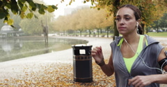 Runner woman running in park exercising outdoors fitness tracker wearable Stock Footage