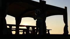 Boy playing with a ball on the veranda at sunset Stock Footage
