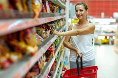 Young woman shopping for cereal, bulk in a grocery supermarket - stock photo