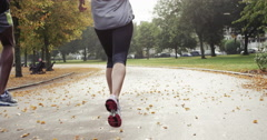 Close up feet running athletic couple runners training in park - stock footage