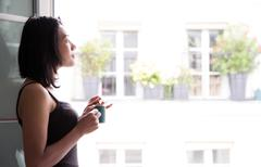 Young woman with drink standing at an open window - stock photo