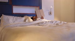 A woman reading a book in comfortable bed at hotel room Stock Footage