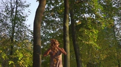 Happy african girl in sunny autumn park throwing up fallen leaves, slow motion. Stock Footage
