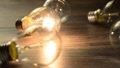 glowing bulb on the brown wooden background. Many lamps and lights up only one. - stock footage