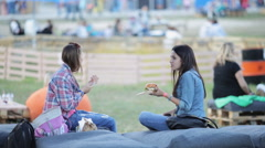 Two beautiful girls eating burgers at the festival of street food Stock Footage
