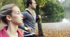 Athletic couple running in park wearing wearable technology connected devices Stock Footage