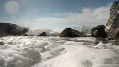 Sea foam in rocky cove with waves breaking on rocks Stock Footage