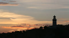 Time lapse at sunrise and silhouettes of  lighthouse on the hill Stock Footage