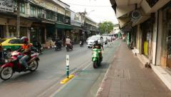 Motorbike drive on bicycle lane, crowded Thanon Tanao street - stock footage