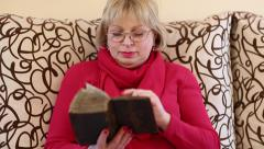 Woman sitting on a divan and reading old book Stock Footage