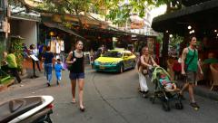 Tourists pass Rambuttri alley, taxi car slowly drive through, POV walk forward Stock Footage