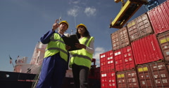 An African American woman discussing logistics with a manager at a shipyard. - stock footage