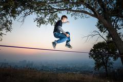Man walking on a tightrope at sunset slackline - stock photo