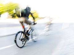 cyclist at high speed in blurred motion - stock photo