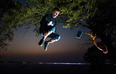 Man walking on a tightrope, jumping into the city night lights slackline - stock photo