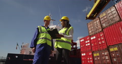 An attractive businesswoman and a manager doing inspections at a busy dock. - stock footage