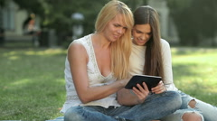 Sitting on the grass using a tablet Stock Footage