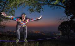 Man walking on a tightrope at sunset slackline Stock Photos