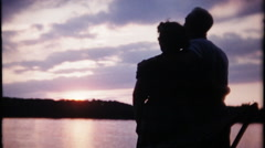 2545 - intimate silhouette, sunset, man & woman, lake - vintage film home movie - stock footage