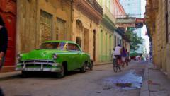 Vintage green car parked in the Habana Vieja district with people walking around Stock Footage