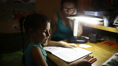 Teen in the evening doing homework girl lessons draws light from the lamp Stock Footage