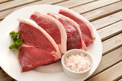 Four uncooked succulent beef steaks - stock photo