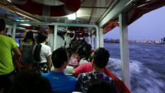 Travel within express boat full of passengers, lean out the hull, dusk river Stock Footage