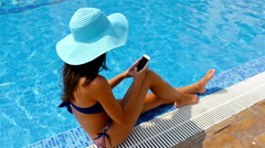 Young woman in swimming suit and blue hat sitting on the edge of a swimming pool Stock Footage