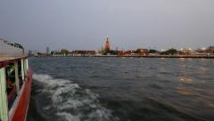 Chao Phraya river west bank at night, Wat Arun illuminated rise above, from boat Stock Footage