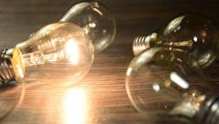 glowing bulb on the brown wooden background. Many lamps and lights up 001342.mp4 - stock footage