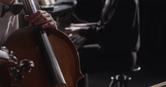 Young man playing double bass and woman playing violin  against background Stock Footage