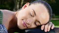 An attractive caucasian woman lying down on a massage bed outdoors Stock Footage
