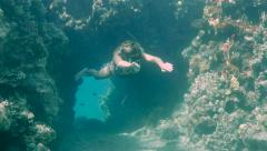female Free  diver Coming out of a tunnel under water - stock footage