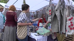 Tourists and citizen women buy natural souvenir clothes at street fair. 4K Stock Footage