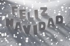 White Feliz Navidad Means Merry Christmas On Snow, Snowflakes Stock Photos