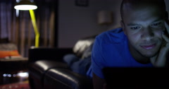An attractive young man streaming a movie on his digital tablet. Stock Footage