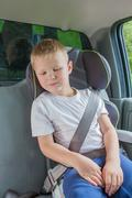 Boy sitting in a car in safety chair fasten by seat belt - stock photo