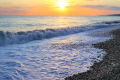 Seashore with pebble beach at sunset sea tide - stock photo