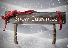 Brown Christmas Sign Snow Guarantee, Snow, Red Ribbon, Snowflake - stock photo