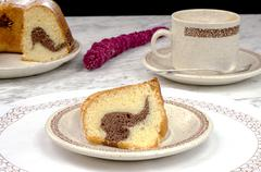 Homemade bundt cake with coffee on marble table - stock photo