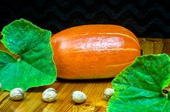 Ripe pumpkins with leaves on a wooden table - stock photo