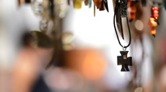 Wooden cross in leather necklace hanging in a display - stock footage