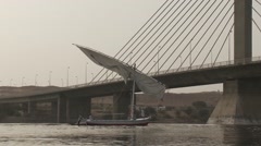 Egyptian felucca sailing boat lowers sail to pass under modern bridge - stock footage