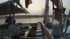 Sailors on Egyptian felucca boat at dusk Stock Footage