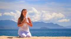 blonde girl demonstrates yoga asana stands on knees - stock footage