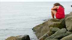 Little girl in red summer dress sitting on the rocks on the sea shore Stock Footage