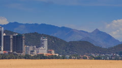 View of resort city against mountains from sand beach Stock Footage