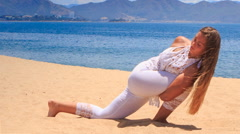 blonde girl in lace shows yoga asana hands lock round leg - stock footage