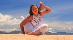 blonde girl in lace shows yoga asana leg behind back - stock footage