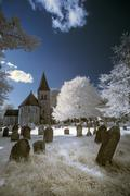 Infrared landscape of old church in churchyard in English countryside - stock photo